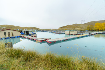 tonnes: TWIZEL, NEW ZEALAND -MAY 6, 2016: Floating Salmon Farm on the glacial waters of Wairepo Arm, NZ. New Zealand accounts for over half of the world production of King Salmon (7,400 tonnes in 2005).
