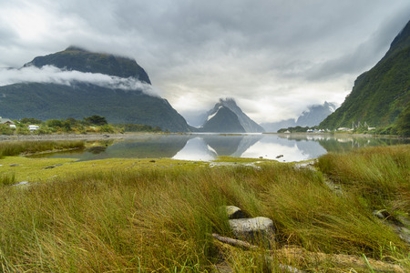 te: Milford Sound (Piopiotahi in Maori) in cloudy day, a fjord within Fiordland National Park, Piopiotahi (Milford Sound) Marine Reserve, and the Te Wahipounamu World Heritage site, New Zealand. Stock Photo