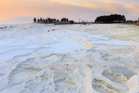 Travertine pools and terraces in evening with crowded tourists in far distance at Pamukkale, Denizli, Turkey.