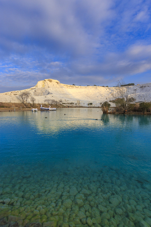 Cleared water lake in morning with calcified limestone terraces mountain of Pamukkale in far distance as background, Denizli, Turkey. Stock Photo