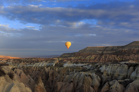 Hot air balloon fly over Cappadocia in early morning, Goreme, Central Anatolia, Turkey. Hot-air ballooning is very popular tourist activity in Cappadocia.