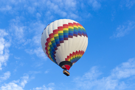 Colorful hot air balloon against blue sky. Stock Photo