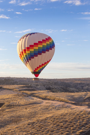 Colorful Hot air balloon fly over grassland valley in Cappadocia, Goreme, Central Anatolia, Turkey. Hot-air ballooning is very popular tourist activity in Cappadocia.