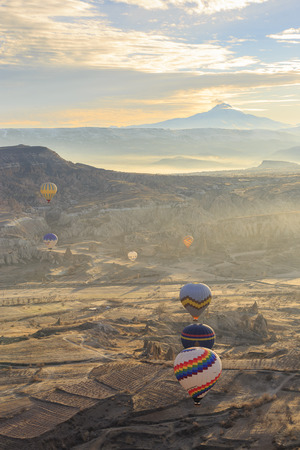 GOREME, TURKEY -JAN 30, 2013: Colorful Hot air balloons fly over Cappadocia, Goreme, Central Anatolia, Turkey. Hot-air ballooning is very popular tourist activity in Cappadocia.