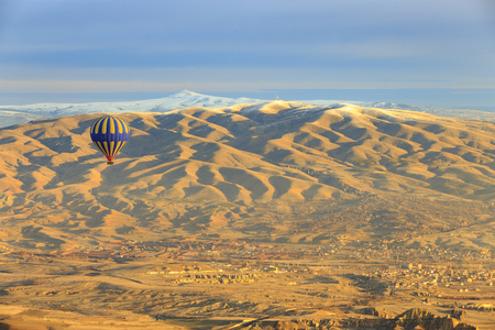 Colorful Hot air balloon fly over Cappadocia near Goreme, Central Anatolia, Turkey. Hot-air ballooning is very popular tourist activity in Cappadocia. Stock Photo