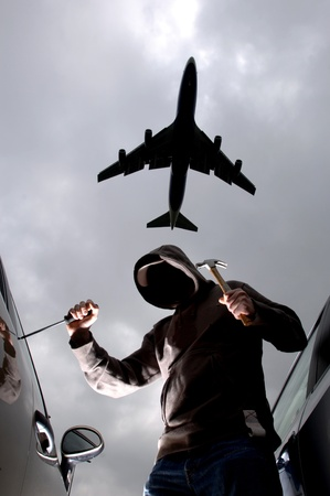 car theft: Thief breaking into parked car while owner on holiday, airliner reflected overhead, and stealing satnav  Stock Photo