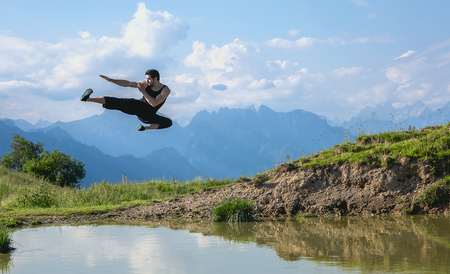 Flying kick on the mountain. martial arts and fitness Stock Photo