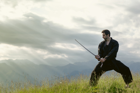 Wushu master with sword, meditation on mountain Stock Photo