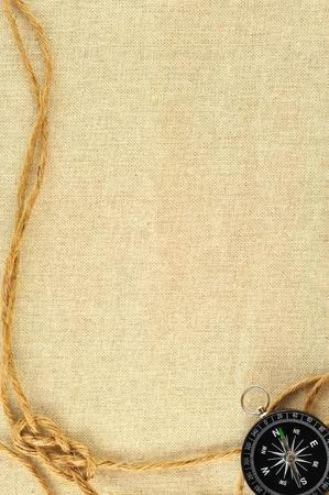 Kompass und Seil auf einer Leinwand aus Sackleinen Standard-Bild - 9784923