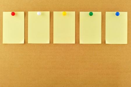 Blank sticky notes pinned on cardboard photo