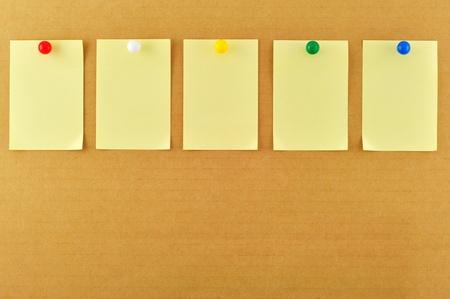 pinned: Blank sticky notes pinned on cardboard Stock Photo