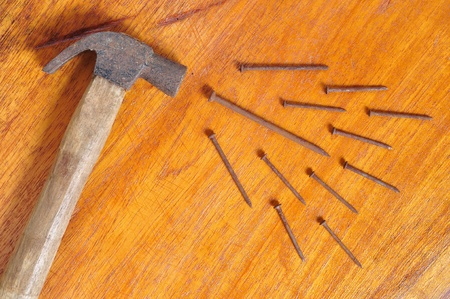Hammer and nails on wooden board photo
