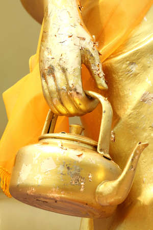Golden Kettle in The Hand of Monk Stock Photo - 7085291