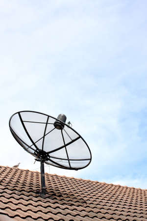 A satellite dish on the roof with blue cloud sky. photo