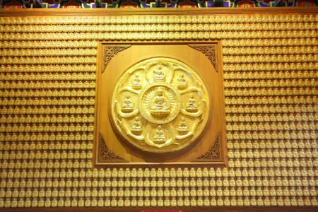 The circle of golden buddha on wood and row of golden buddha doll. photo