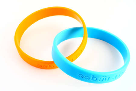 wrists: Yellow and light blue rubber bracelet. Yellow is colour of King, light blue is Queen of  Thailand. Stock Photo