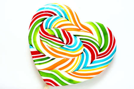 sugarplum: Close up of colourful lollipop, heart shape. Stock Photo