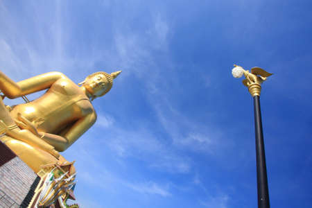 Electric post and big golden buddha with blue sky, Ang Thong province, Thailand. photo