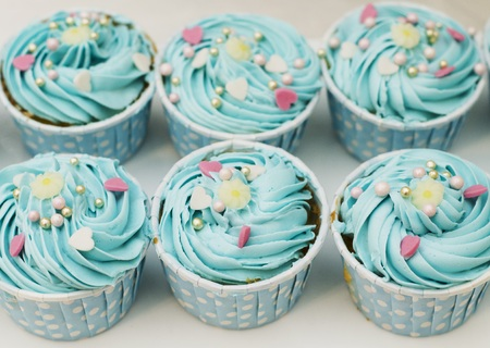Cup cake with blue cream close up sweet food background photo