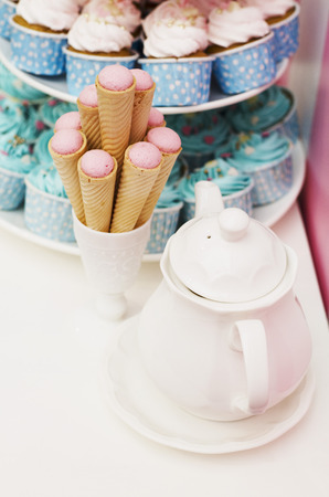 cake background: Roll sweet in cup and white kettle and cup cake background