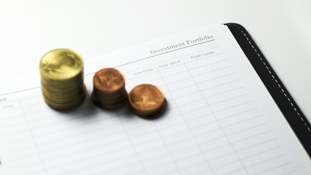 Investment portfolio books and coins currency for business concepts