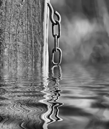 metal chain: Metal chain hanging from a post with a water reflection.