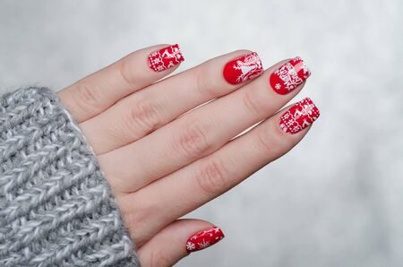 red Christmas manicure with deer and snowflakes and Norwegian pattern Stock Photo