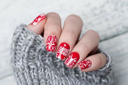 red Christmas manicure with deer and snowflakes and Norwegian pattern