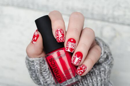 red Christmas manicure with deer and snowflakes and Norwegian pattern Imagens