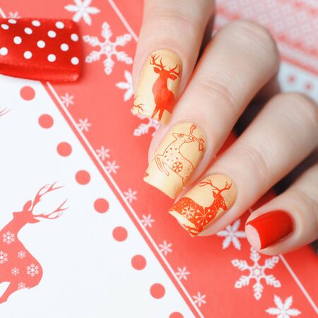 Red Christmas manicure with deers on the background of the gift box Imagens