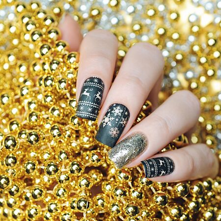 Christmas manicure with deer and snowflakes on gold background