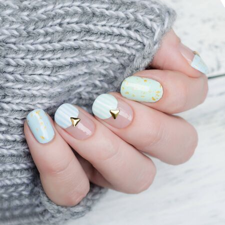 gentle mint blue manicure with gold glitter, stripes pattern and metal rivets Imagens