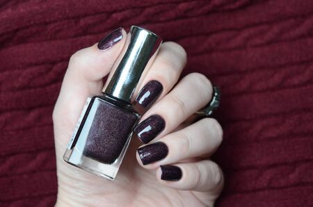 Burgundy wine manicure with a shimmer and ring on knitted sweater background