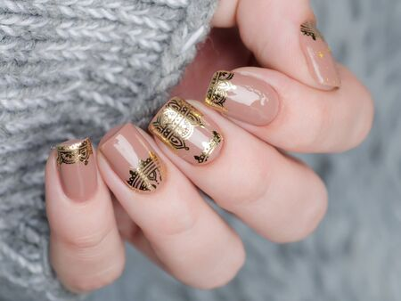 beige manicure with gold lace pattern on gray background