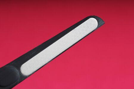 black metal lazer nail file manicure on neon pink background