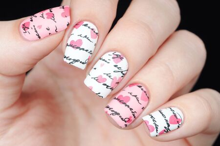 White pink manicure on St. Valentine s Day with pattern letter and hearts Stock Photo