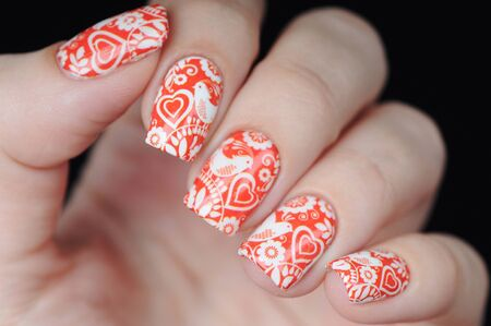Red manicure on St. Valentine s Day with white hearts pattern Banco de Imagens