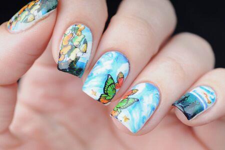 blaue Maniküre mit Schmetterlingsmuster mit Wolken, Ozean und Schiff Standard-Bild