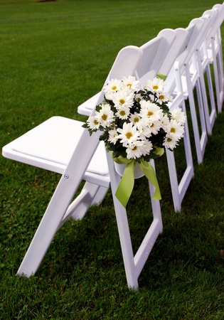 A row of seating arrangements for guests at an outdoor summer wedding.