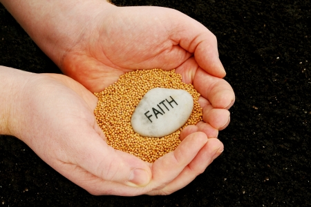 religious text: A religious concept photo that uses mustard seeds and an engraved faith stone held over soil, to illustrate an idea of planting seeds of faith. Stock Photo