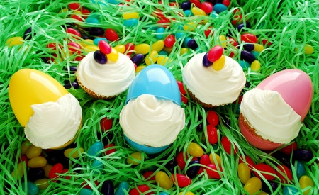 Cupcakes displayed in Easter eggs. Set on Easter grass with abundant egg shaped candies. 스톡 콘텐츠