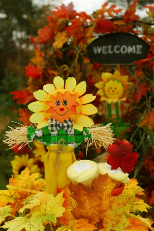 autumn scarecrow: Thanksgiving or festive autumn display with a scarecrow, cupcakes, and a welcome sign in the background