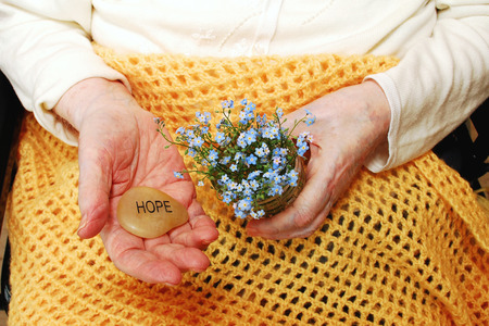 Elderly woman holds forget-me-not flowers and the word Hope, engraved on a stone  Image created to support organizations and people who seek solutions for memory loss  photo