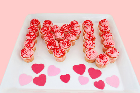 short phrase: A tray of strawberry cupcakes presented to say, I Love You for Valentines or anniversaries.
