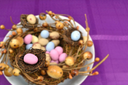 Easter eggs inside a decoration that looks like bird nests. The focus is on a single pink Easter egg inside a small nest. Banque d'images