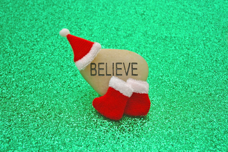 believing: Small Santa hat and boots on an engraved stone, Believe, with a sparkly green festive backdrop. A conceptual image about believing in Santa Claus.