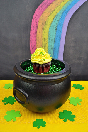 end of rainbow: Saint Patricks Day inspired red velvet cupcake inside a cauldron at the end of a rainbow. Rainbow was drawn on a chalkboard with pink, orange, yellow, green, and blue glitter chalk, plus regular purple chalk.