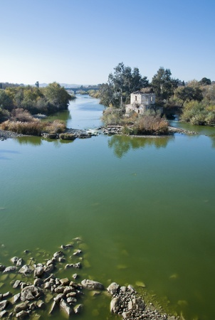 An old watermill on the river in Cordoba with a bridge in the distance.