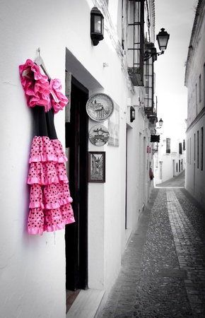 A typical rustic Spanish street edited to show the vibrant colours of the Flamenco dress hanging outside