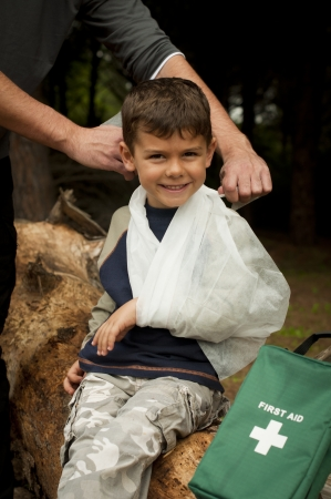 treating: First Aid treatment given to a young boy in the forest, showing an arm sling and a head injury.
